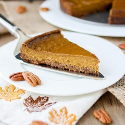 Front view of a slice of vegan pumpkin pie with pecan crust on a white plate