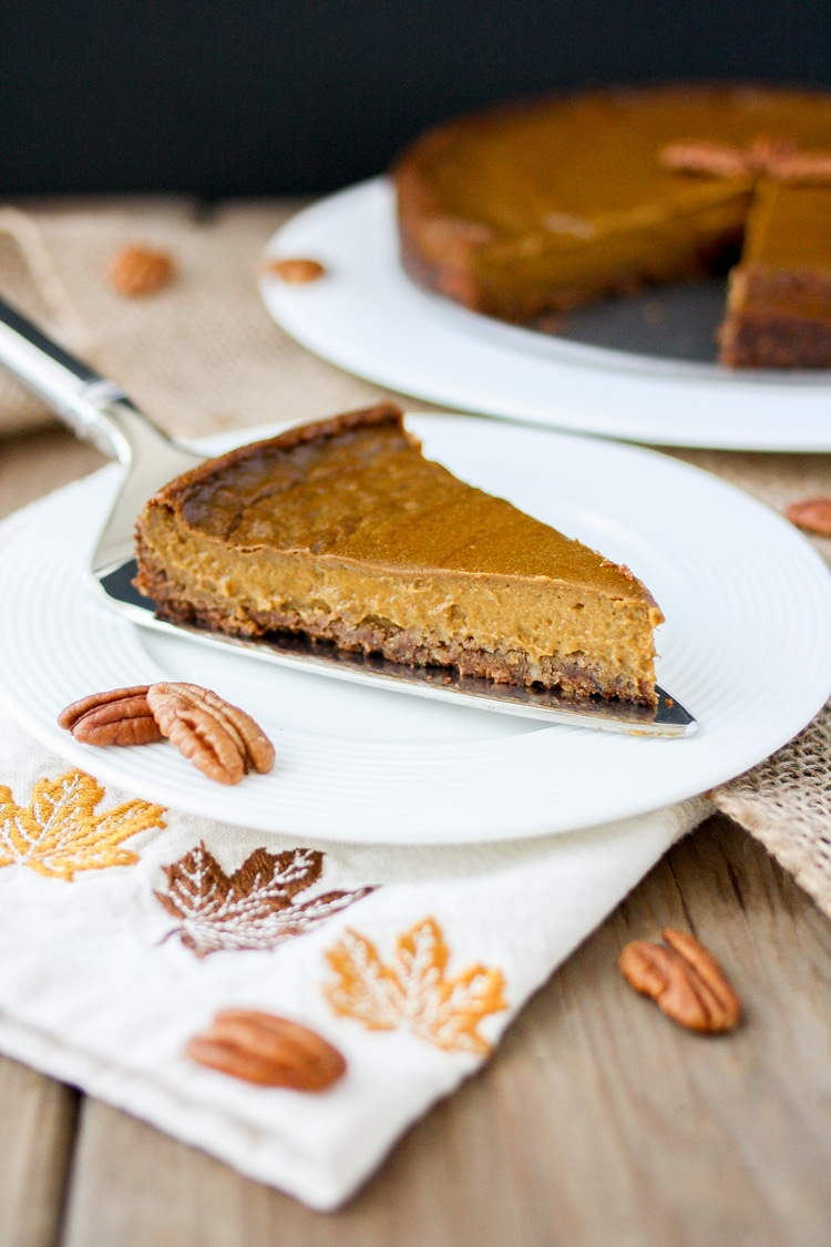 Front view of a slice of vegan pumpkin pie with pecan crust on a plate sitting on napkin