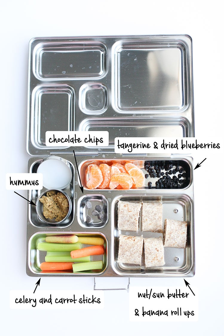 Metal lunchbox with veggies, hummus, tortilla rolls, and fruit
