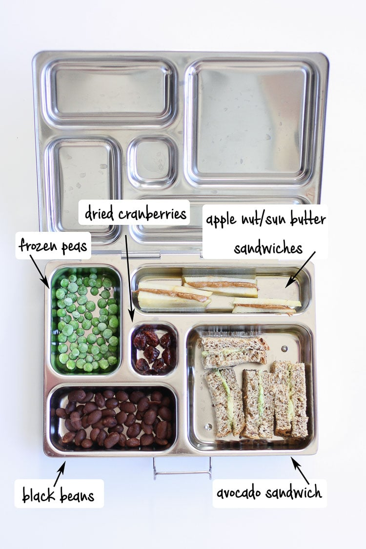 Metal lunchbox filled with veggies, beans, apples and peanut butter and sandwich slices