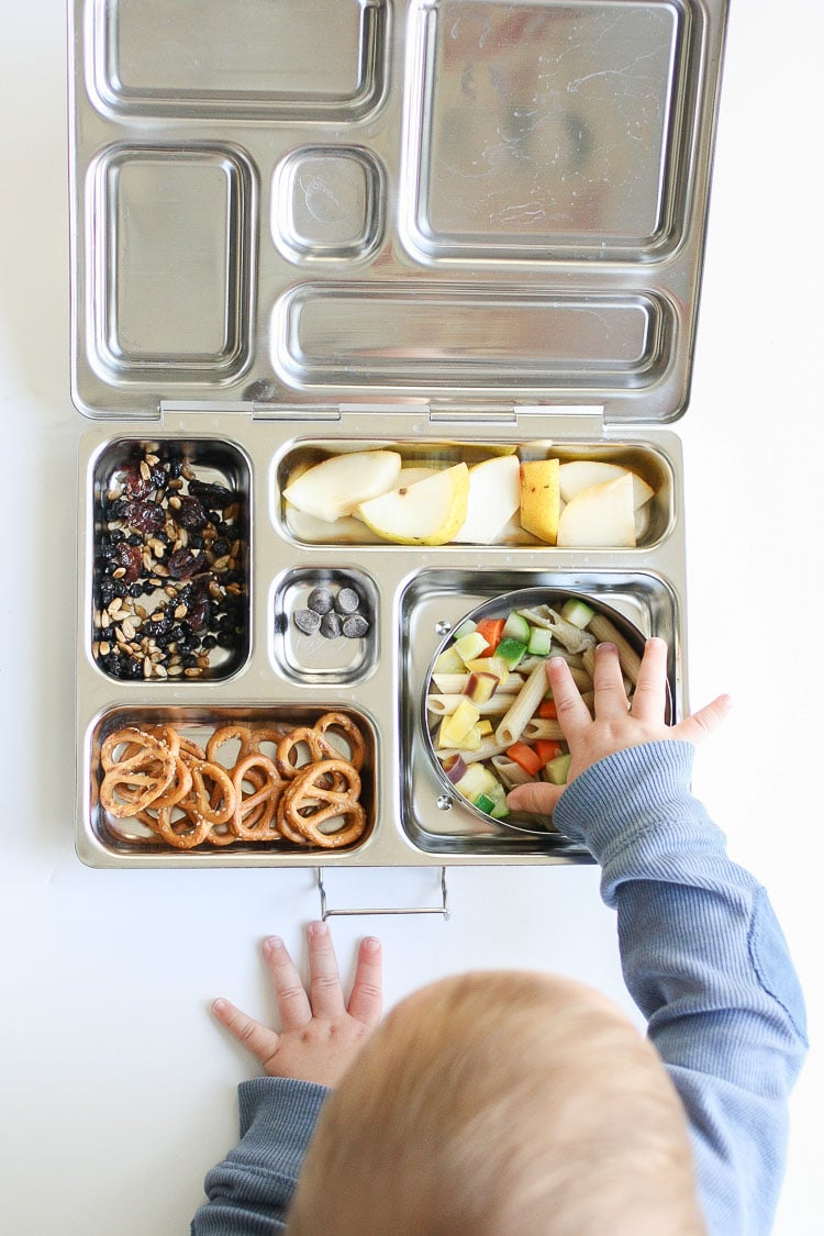 Baby crawling toward lunchbox with food and reaching in