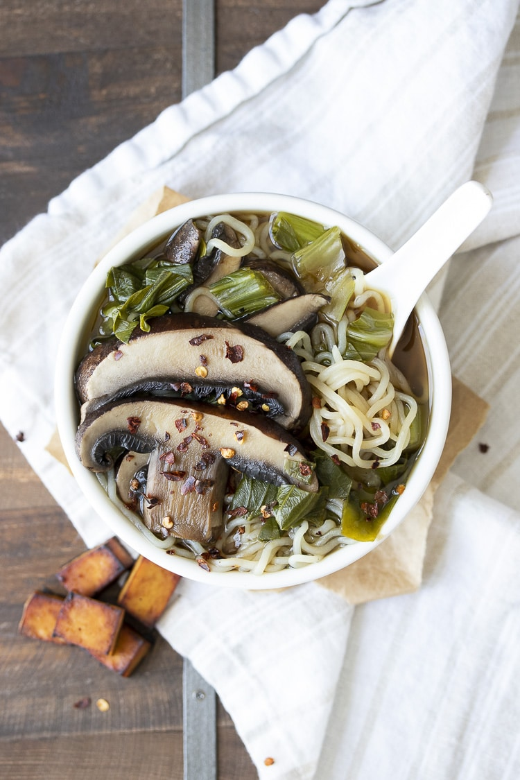 White bowl filled with miso soup, bok choy, portobello mushrooms and noodles