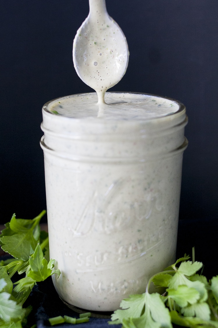 Spoon coming out of a glass jar filled with creamy white sauce