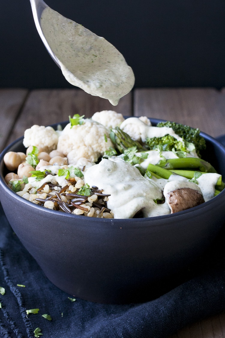 Spoon drizzling white sauce on top of veggies, rice and beans in a black bowl