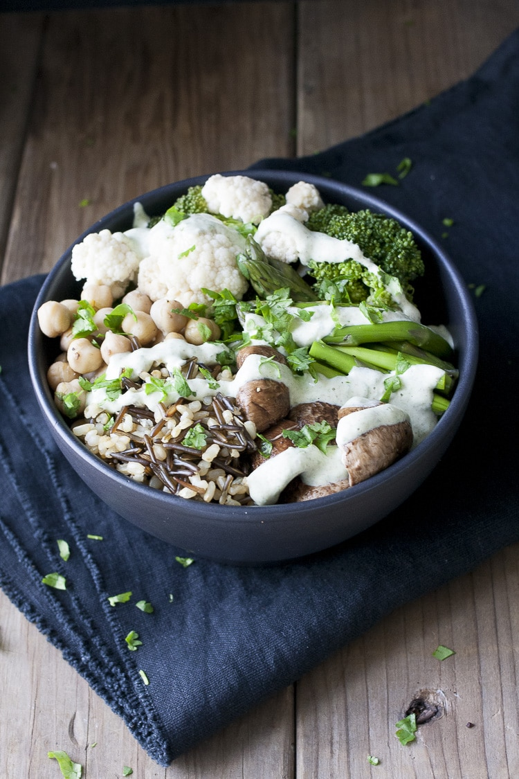 Veggie rice bowl with lemon herb sauce veggies dont bite black bowl with different veggies rice and beans drizzled with white sauce forumfinder Image collections