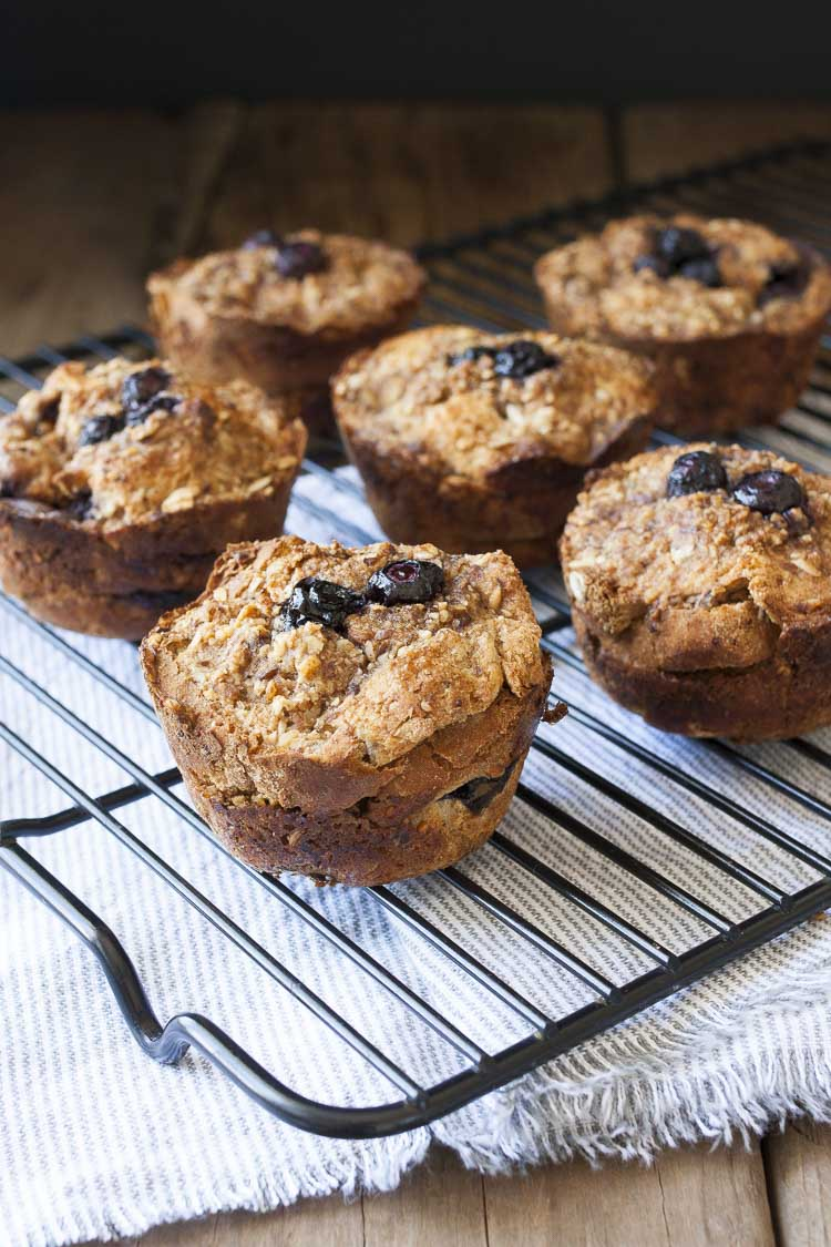 Wire cooling rack filled with blueberry french toast muffins sitting on grey striped towel
