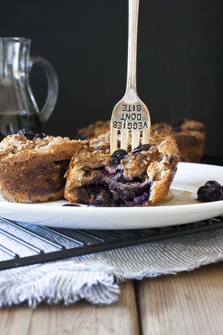 Fork stabbed in the top of a half eaten blueberry french toast muffin