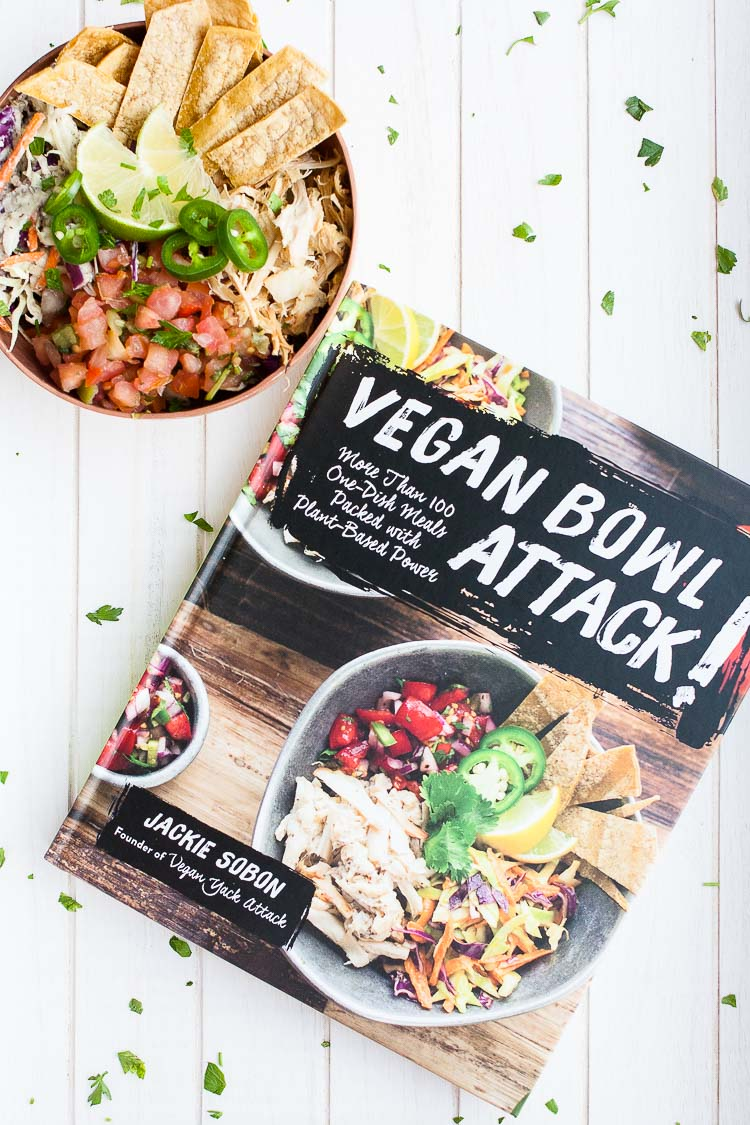 An overhead shot of a vegan taco bowl and vegan bowl attack cookbook sitting on a white wooden surface