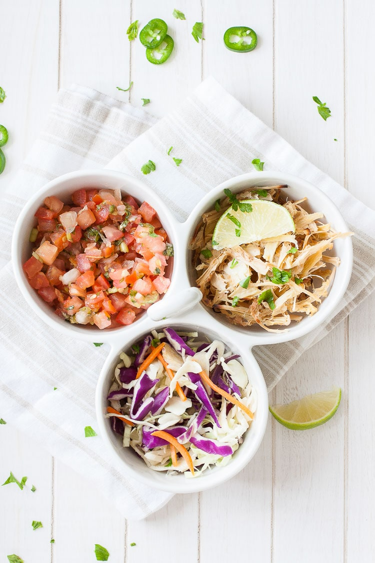 An overhead shot of three bowl filled with vegetables to make a vegan fish taco bowl