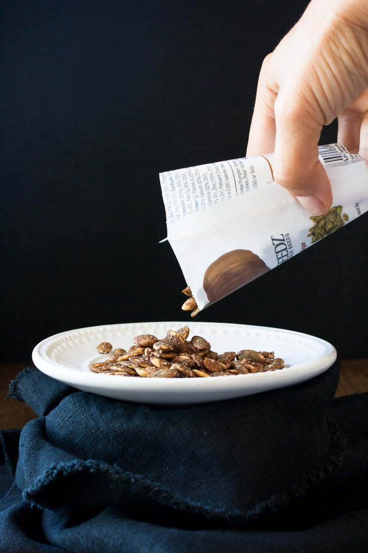 A hand pouring cinnamon pumpkin seeds from a packet to a plate