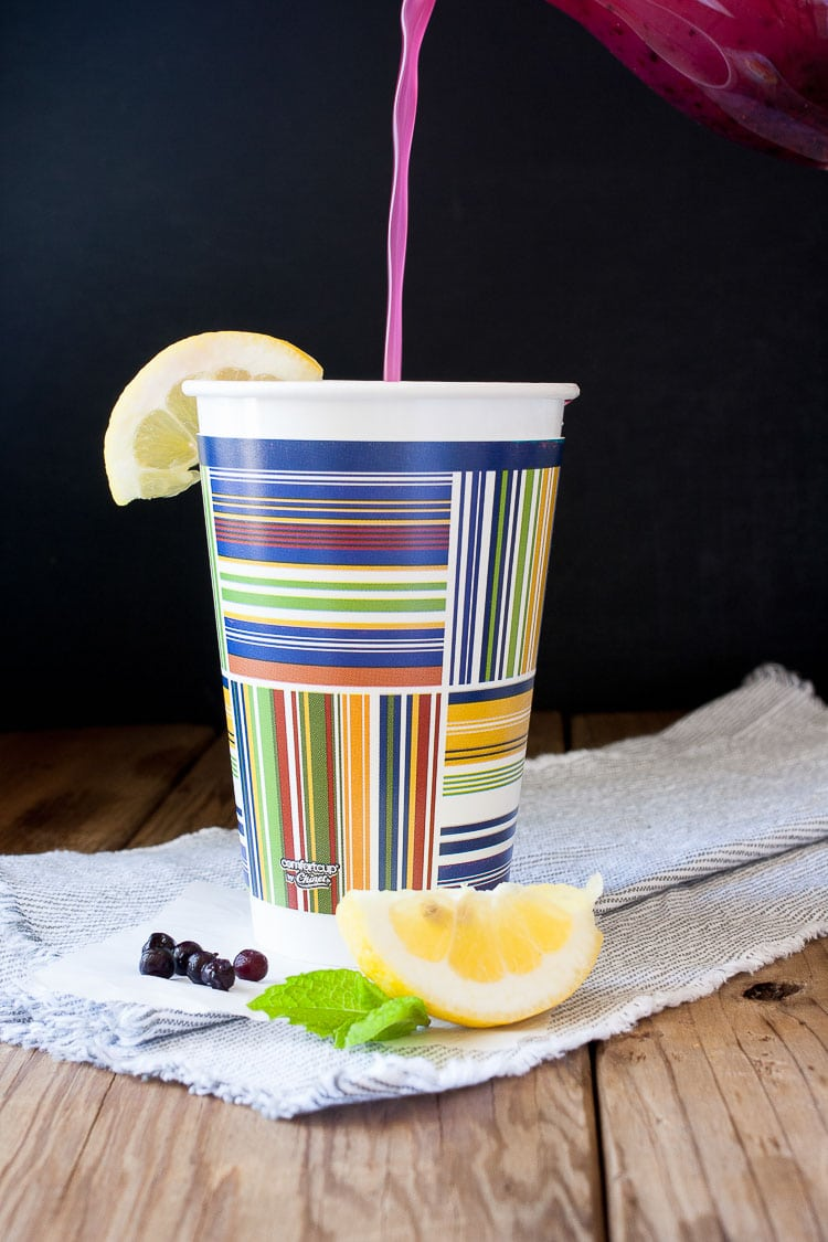 Pouring blueberry mint lemonade in a disposable colorful coffee cup