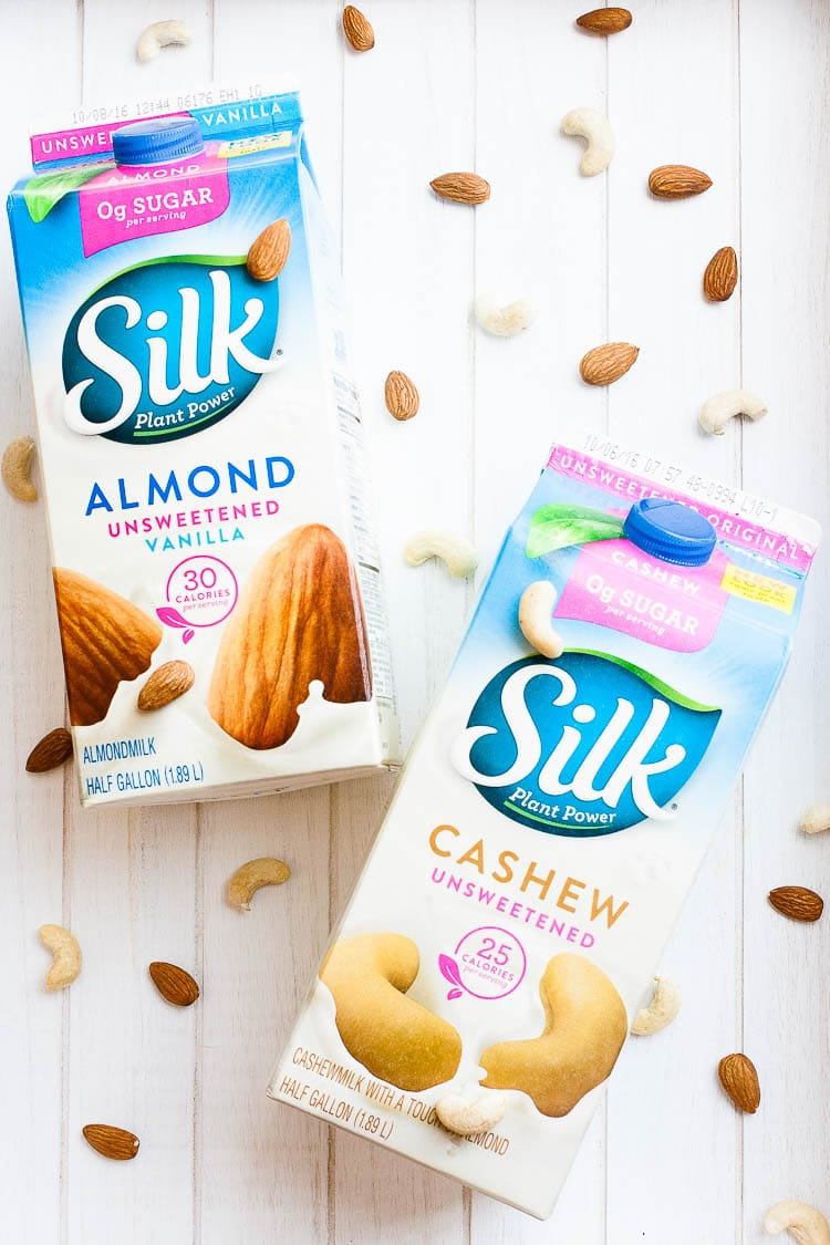 An overhead shot of colorful almond and cashew milk half gallon cartons