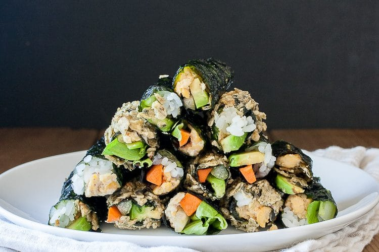 vegan sushi rolls stacked on a white plate