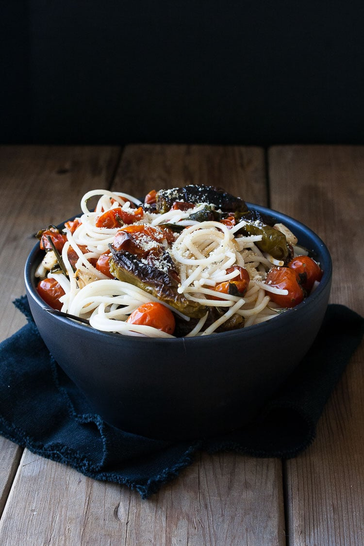 A bowl of spaghetti with charred tomatoes and peppers
