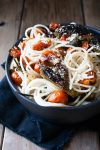 Spaghetti in a bowl with charred tomatoes and peppers