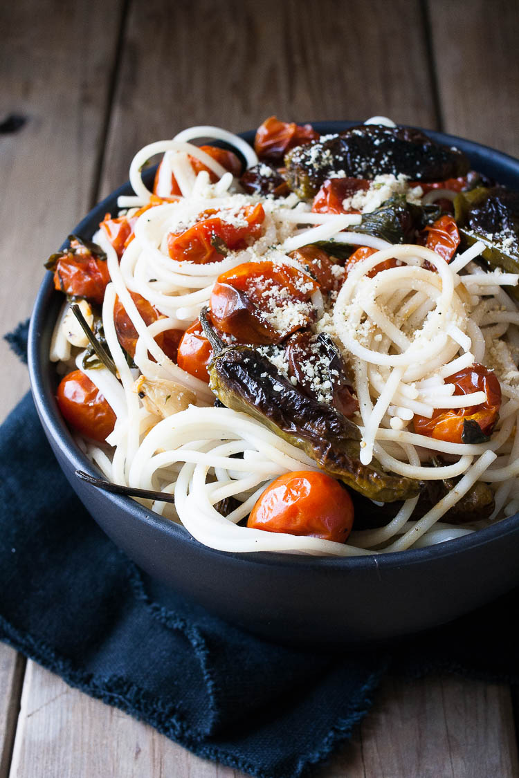 A close up shot of spaghetti in a bowl with charred tomatoes