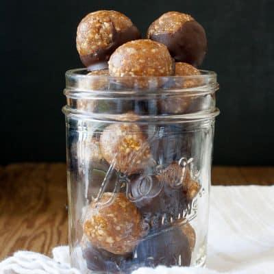 A glass jar filled with Raw Vegan Caramel Peanut Protein Truffles