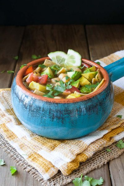 A blue bowl filed with Vegan Chickpea Soup sitting on a wooden surface and topped with lime wedges