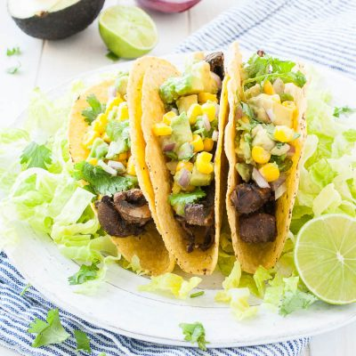 three tacos on a white plate topped with salsa