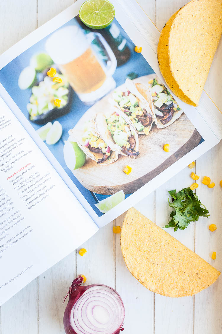 A cookbook open at Beer-Marinated Portobello Mushroom Tacos sitting on a wooden surface