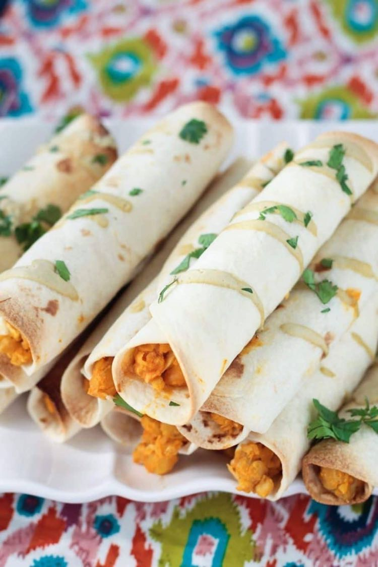 Taquitos with buffalo sauce chickpea filling piled on a white plate