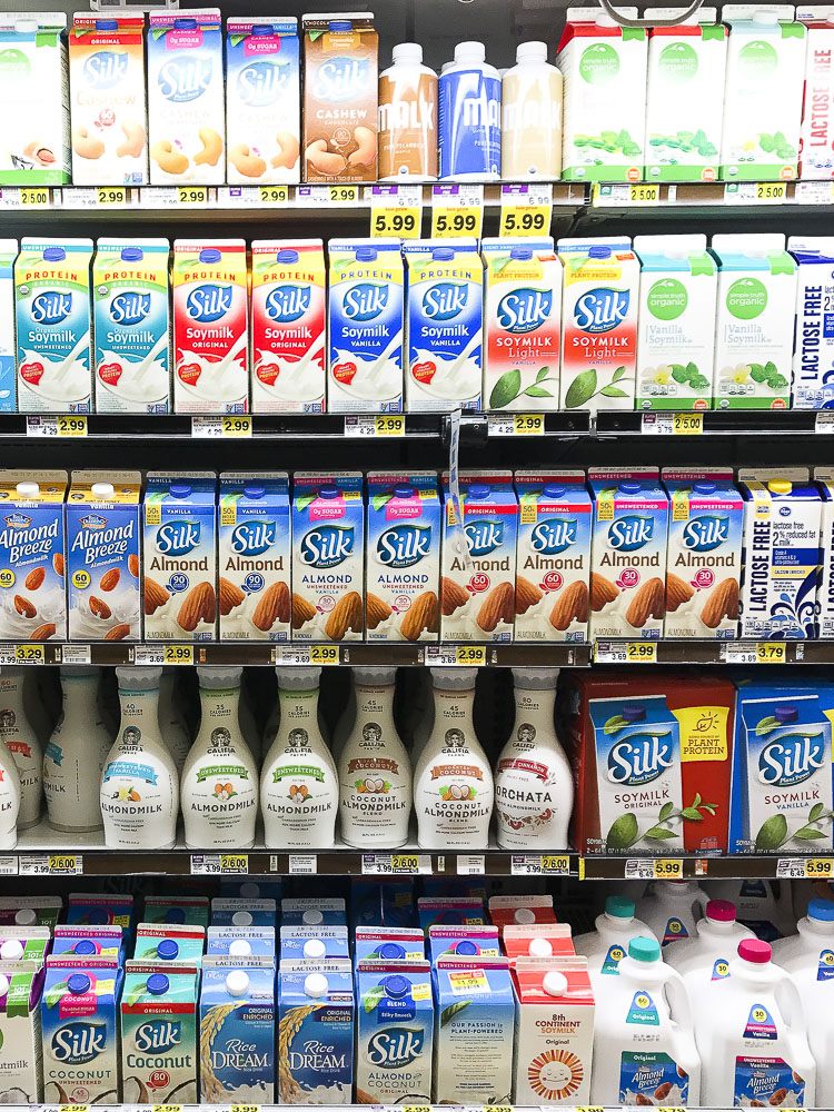 A photo of a supermarket shelf filled with nut milk