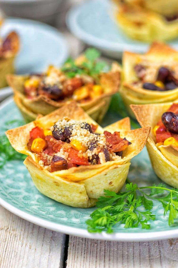 Crispy tortilla cups filled with beans and salsa on a light blue plate