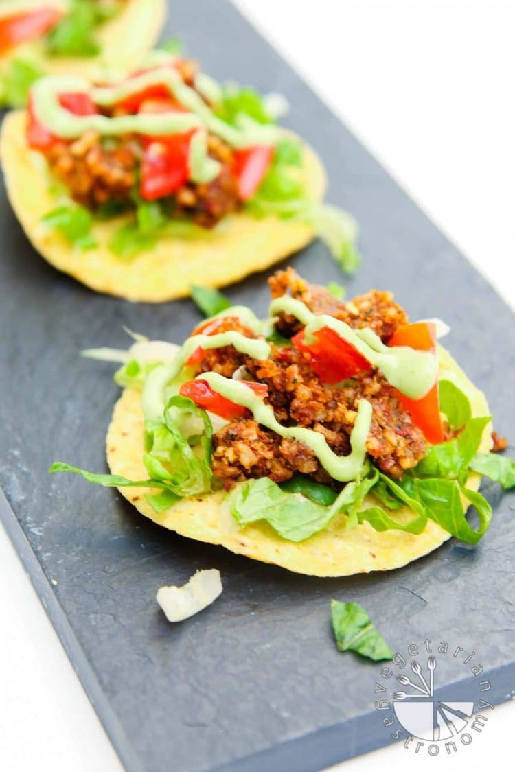 Crispy corn tortilla topped with lettuce, walnut tomato crumble and creamy green sauce