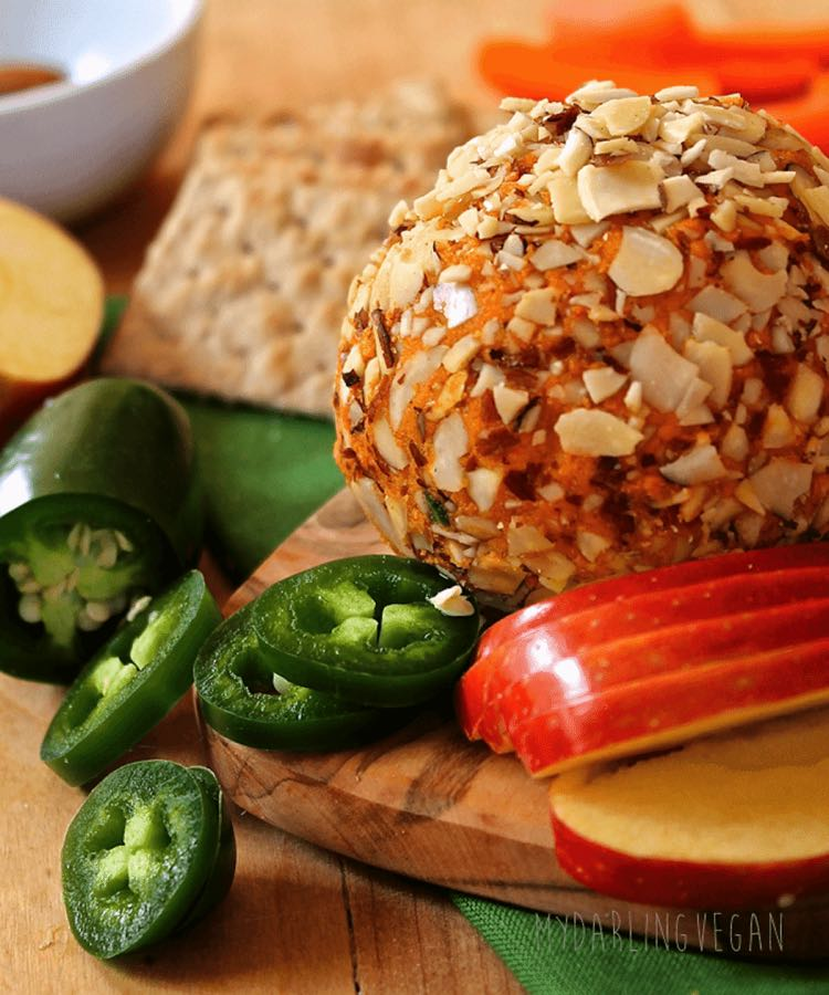 Cheese ball rolled in sliced almonds on a board with sliced apples and jalapeños