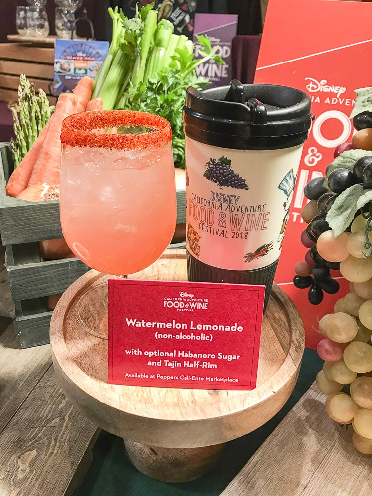 Glass of watermelon lemonade next to a Disneyland Food and Wine Festival tumbler