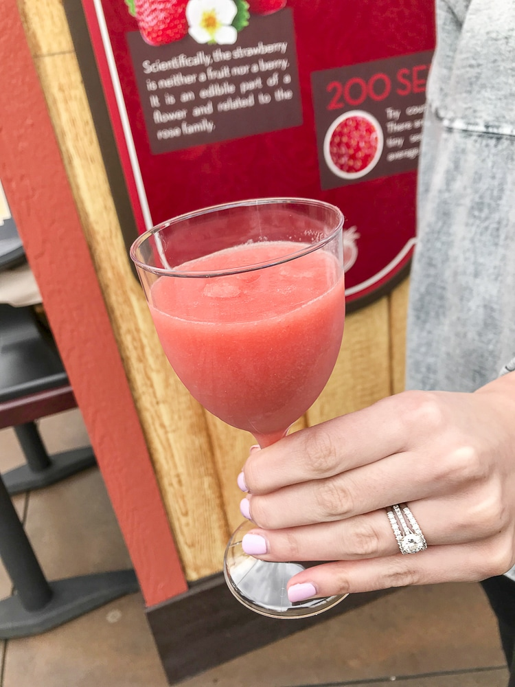 Hand holding plastic wine glass filled with blended frozen strawberry drink