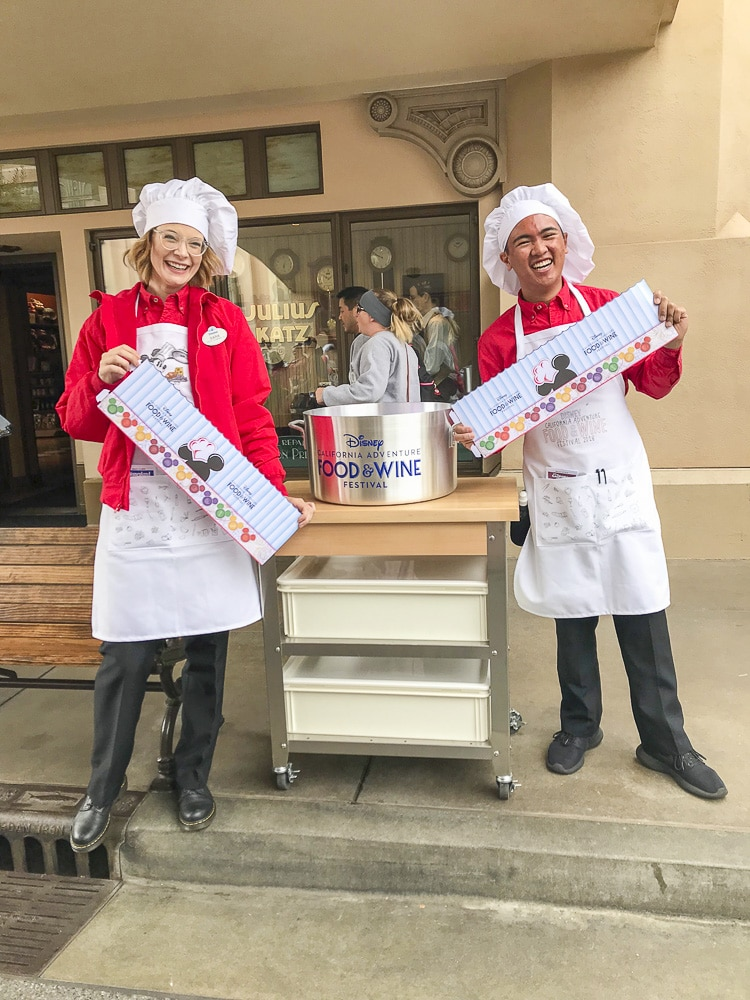 Two Disney workers wearing chef hats holding paper signs standing next to a cart