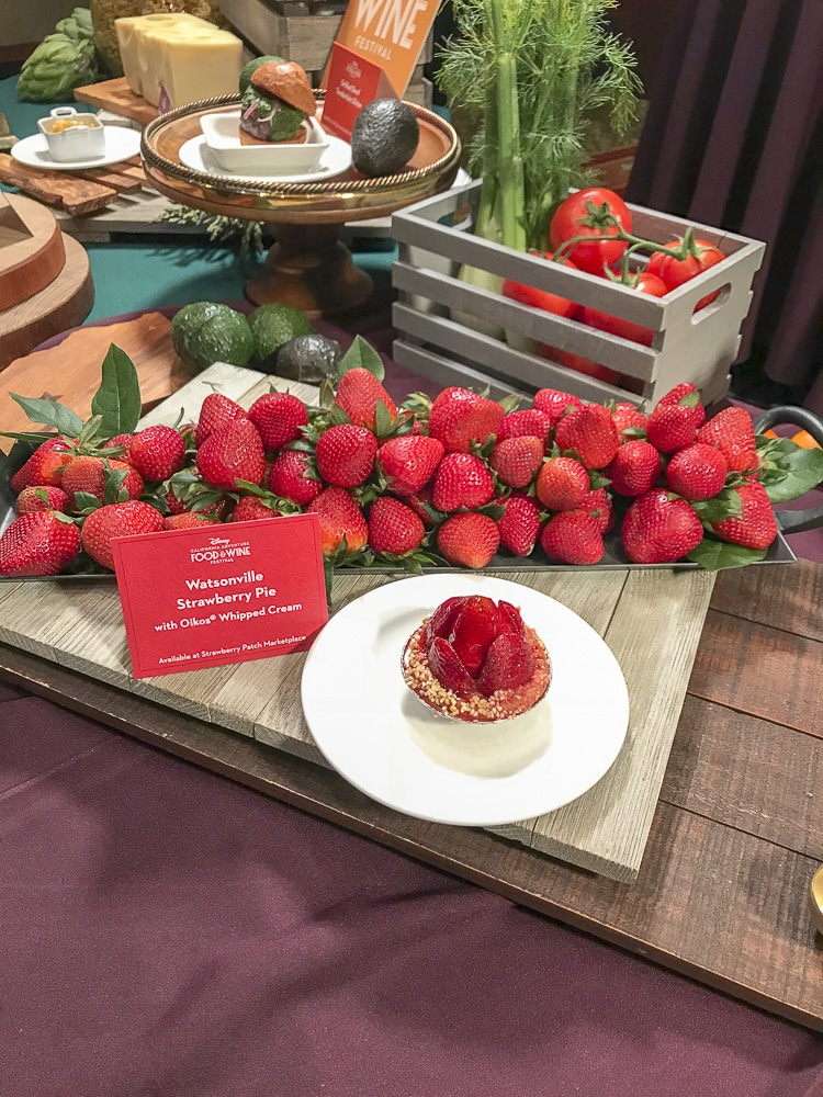 Plate with mini strawberry pie in front of platter of fresh strawberries
