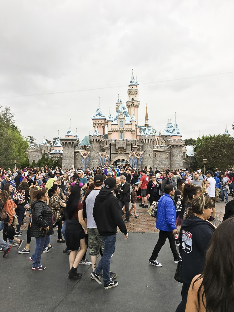 Front view of the Disneyland Cinderella castle with a crowd of people during the day