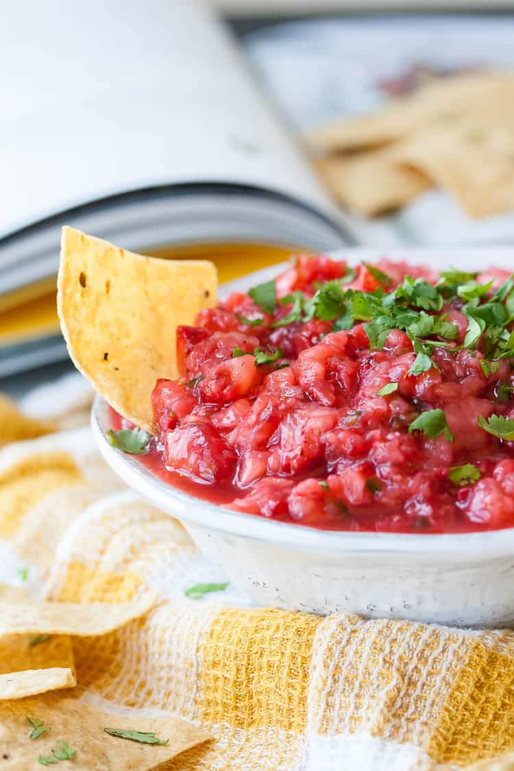 Salsa made from strawberries, chile, minced onion, lime and salt in a small bowl with chips at the side