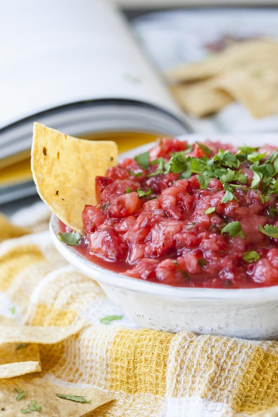 A close up of spicy strawberry salsa in a bowl with a chip