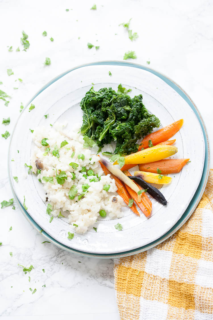 sautéed spinach and kale mix with mushroom risotto and carrots on a white plate