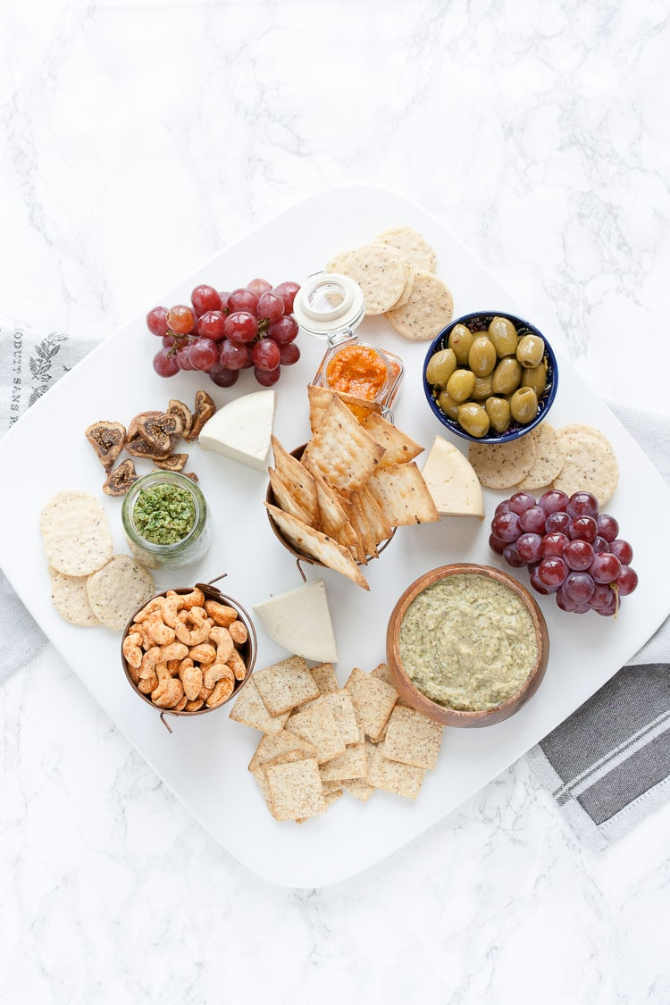 An overhead shot of a vegan cheese and dip platter on a marble surface