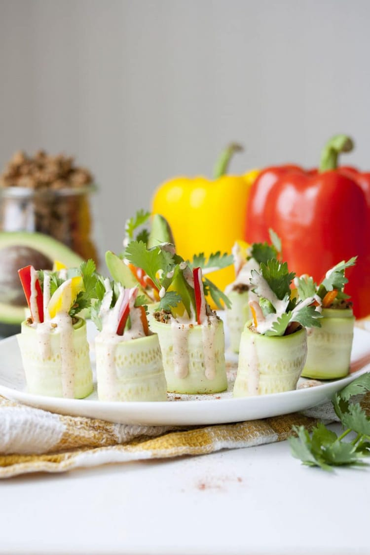 a side view of rolled zucchini appetizers on a white serving plate