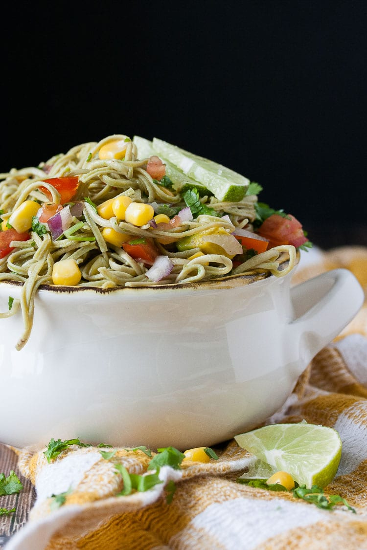 A side shot a mexican pasta salad in a white bowl topped with lime wedges