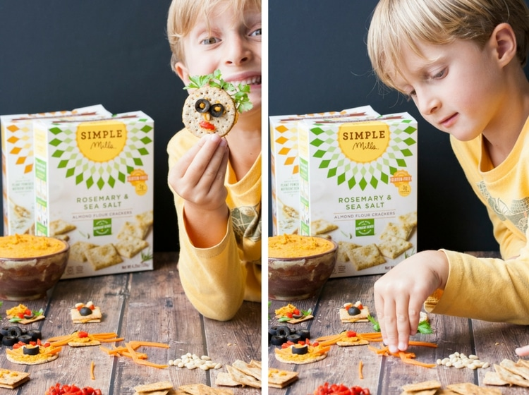 Front view of child decorating crackers with veggies and hummus and child holding cracker face