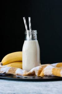 Vegan banana milk in a glass milk bottle with two straws