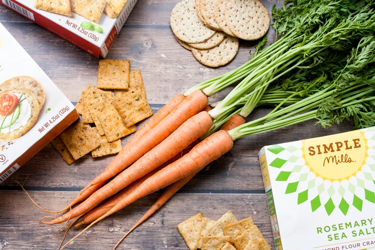 Top view of raw carrots with stalks on table surrounded by crackers and cracker boxes