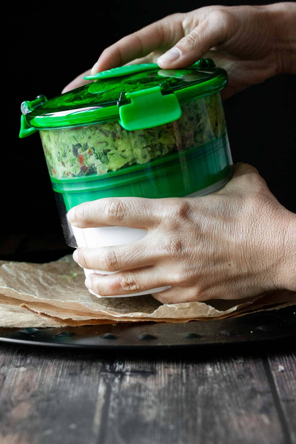 Two hands closing a storage container filled with guacamole and vegan cotija cheese