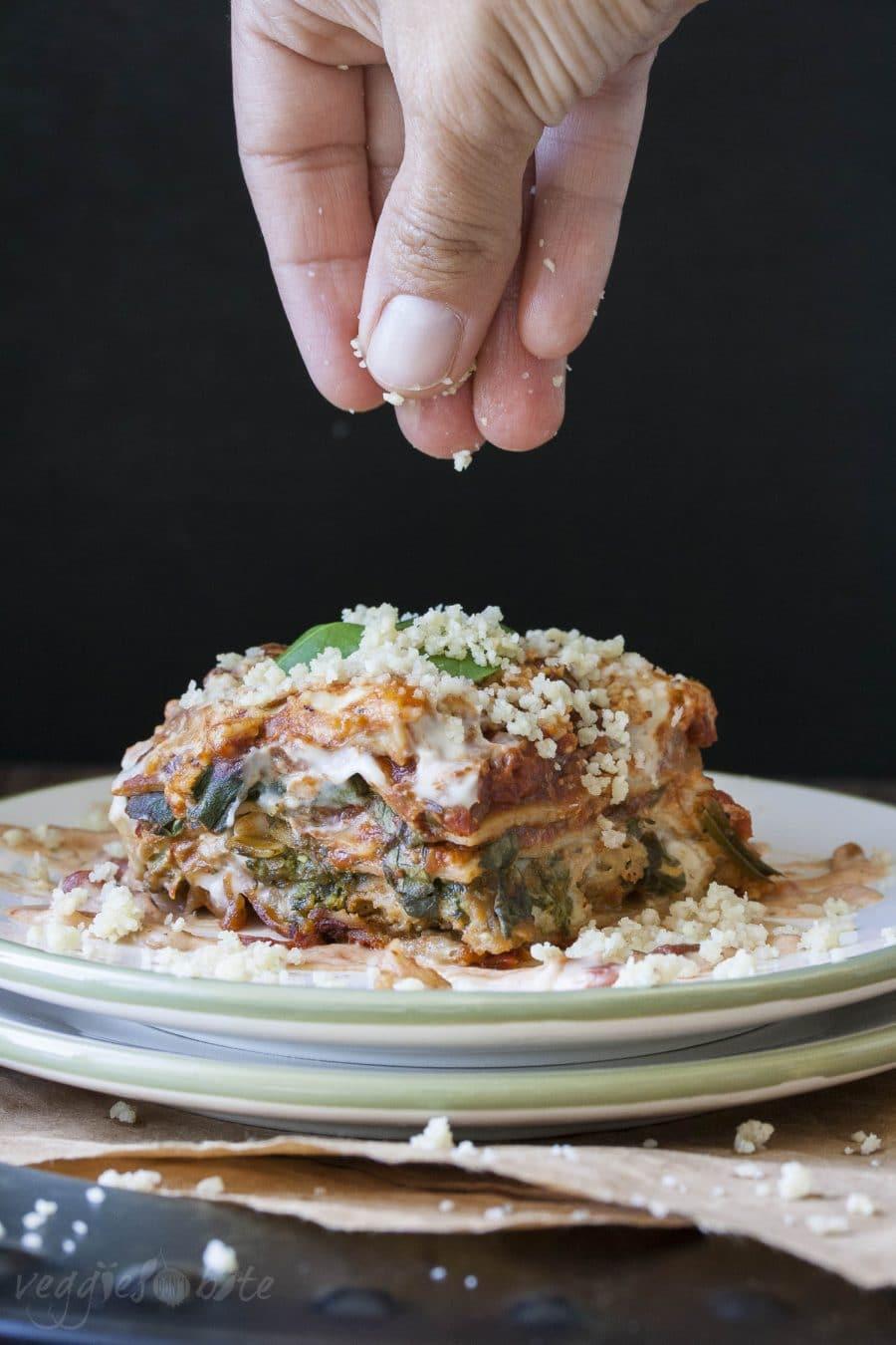 Hand sprinkling vegan parmesan cheese on top of lasagna