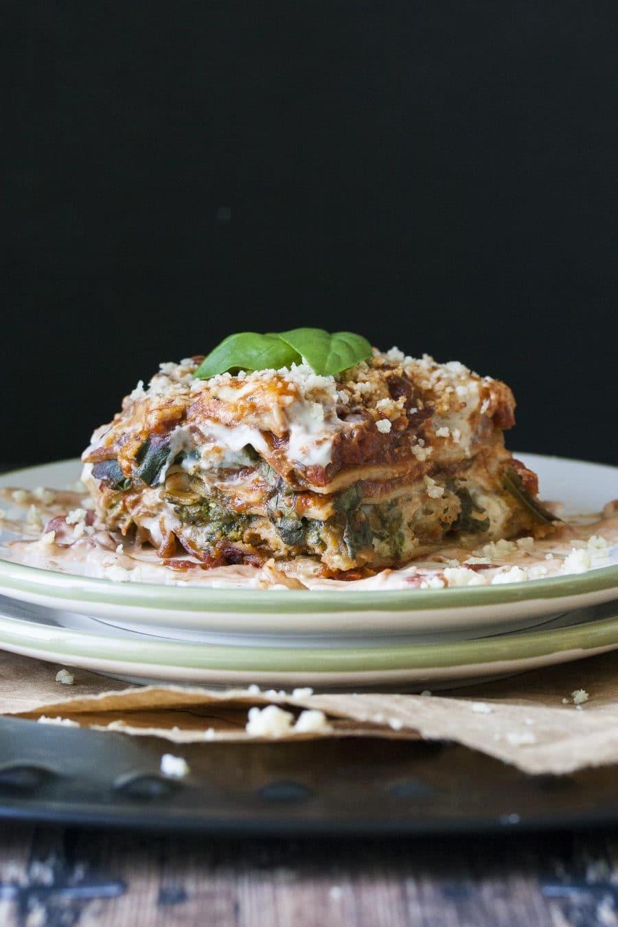 Piece of vegan creamy pesto, tomato and sausage lasagana on two stacked plate