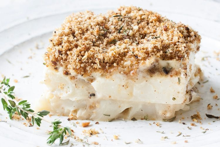 A close up shot of a slice of scalloped cauliflower bake on a plate with a sprig of thyme