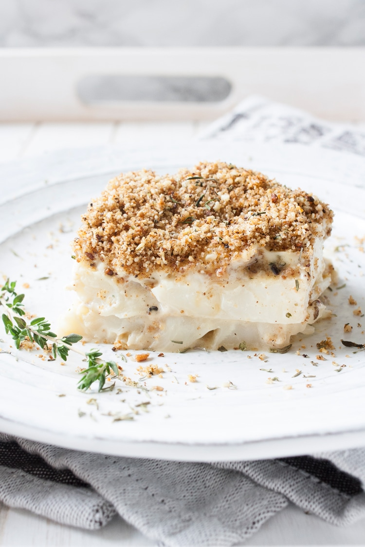 Layered baked creamy cauliflower pieces with breadcrumb topping