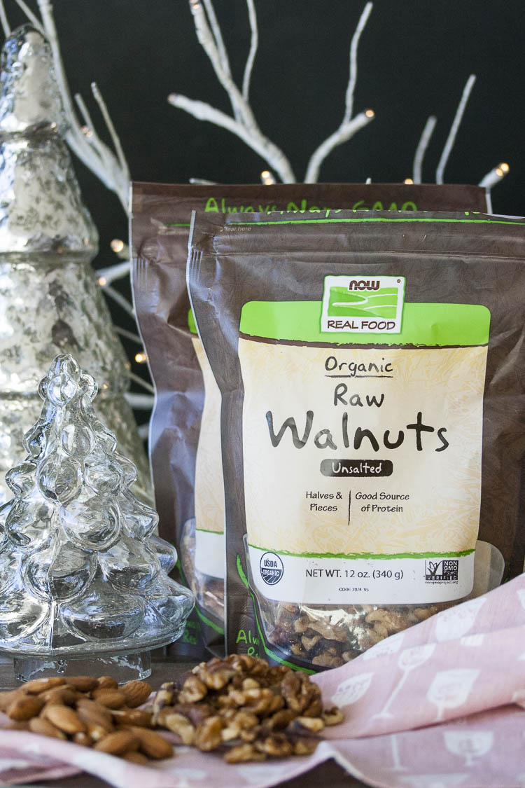 Two packages of NOW Foods walnuts and almonds surrounded by winter holiday decor