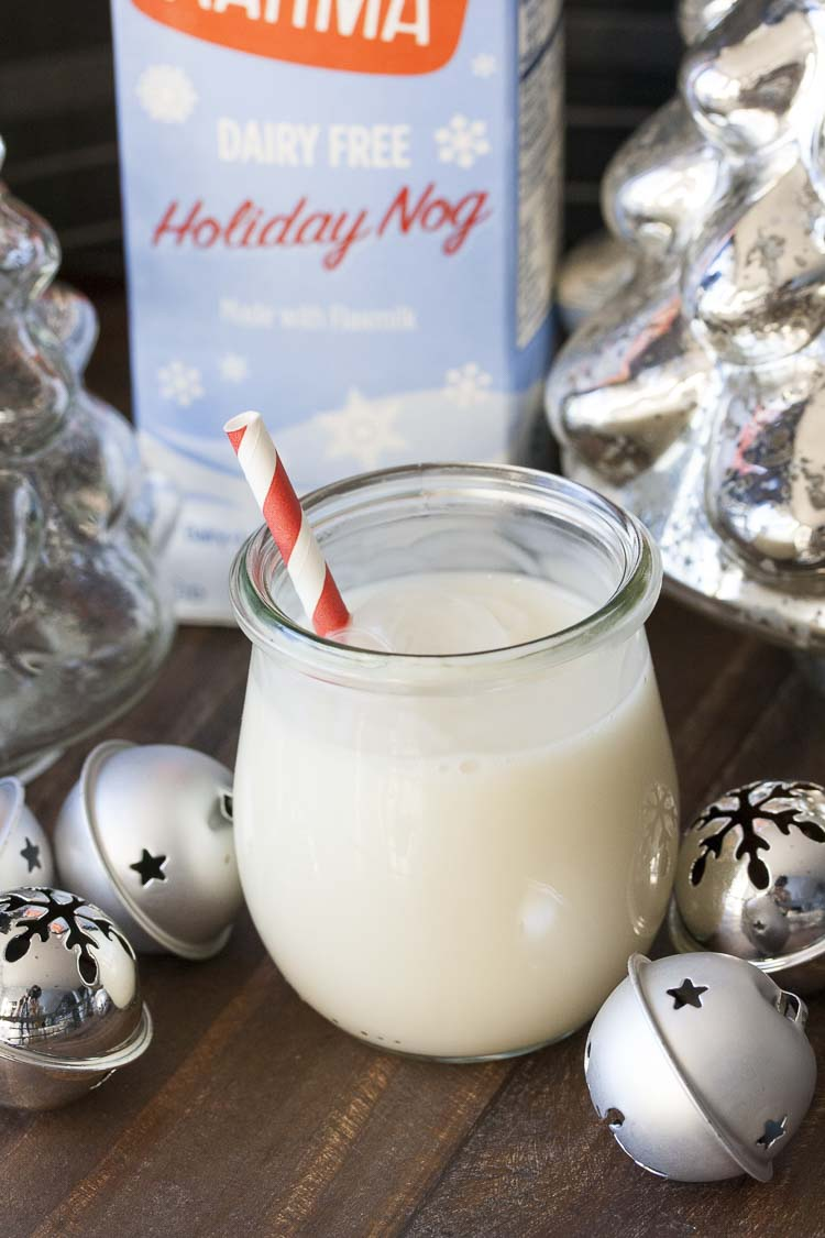 Glass jar of egg nog with a striped red straw surrounded by Christmas decorations